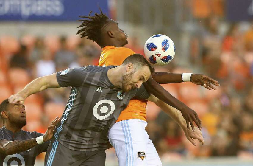 Minnesota United defender Brent Kallman (14) and Houston Dynamo forward Alberth Elis (17) battle for a header during first half of an MLS game at BBVA Compass Stadium Saturday, July 7, 2018, in Houston.