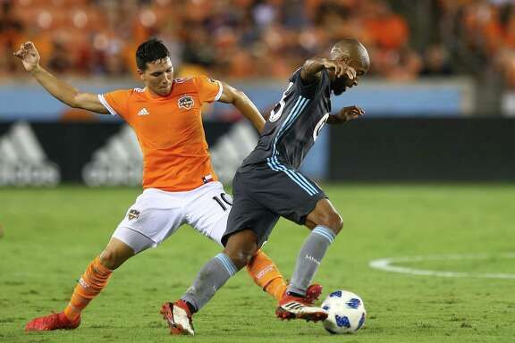 Houston Dynamo midfielder Tomas Martinez (10) tries to poke the ball away from Minnesota United midfielder Collen Warner (26) during the second half of an MLS game at BBVA Compass Stadium Saturday, July 7, 2018, in Houston.