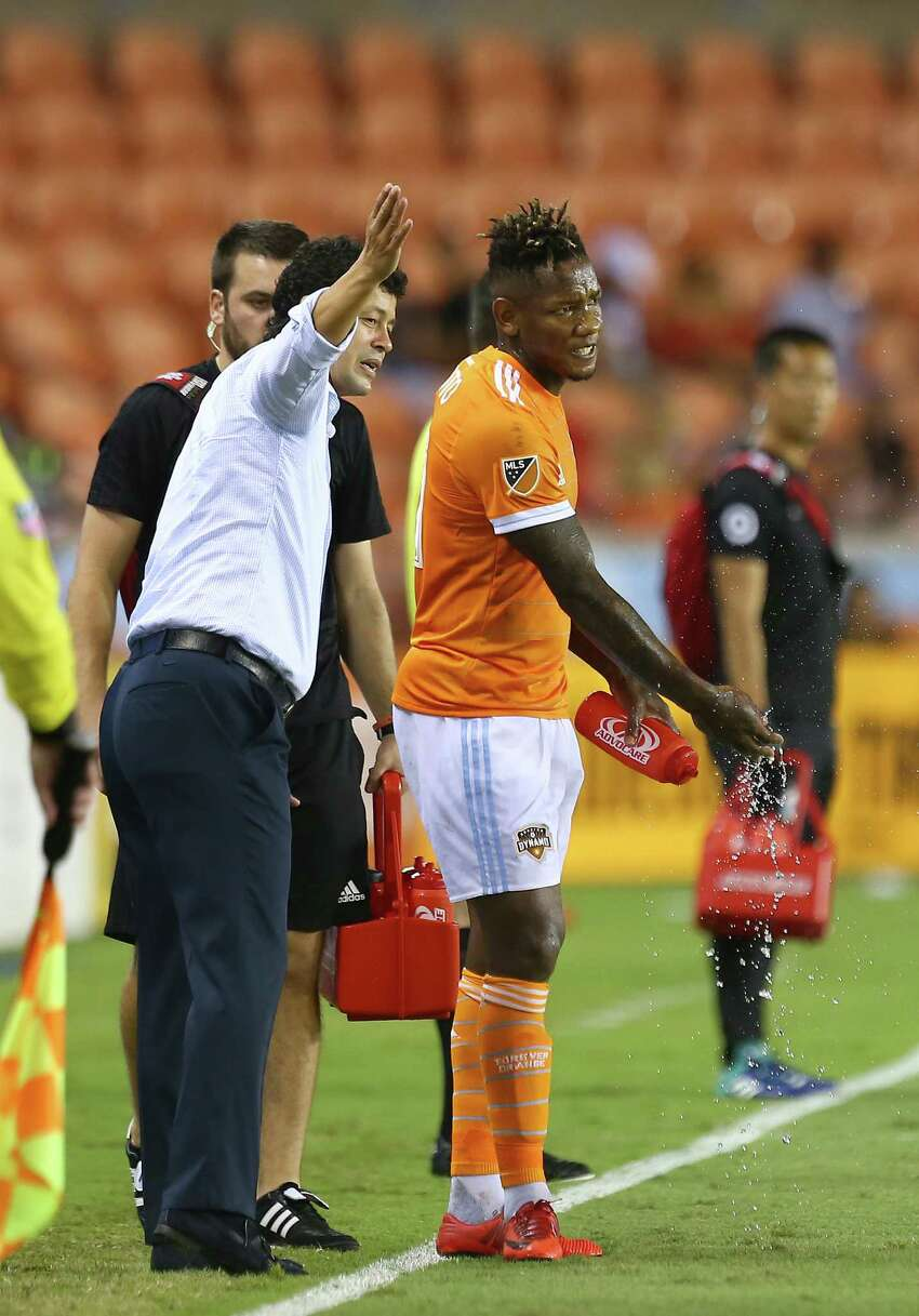Houston Dynamo manager Wilmer Cabrera, left, talks with forward Romell Quioto (31) during an injury timeout in the second half of an MLS game against the Minnesota United at BBVA Compass Stadium Saturday, July 7, 2018, in Houston.