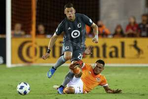Houston Dynamo midfielder Darwin Ceren (24) pokes the ball away from Minnesota United forward Christian Ramirez (21) with a slide tackle during first half of an MLS game at BBVA Compass Stadium Saturday, July 7, 2018, in Houston.