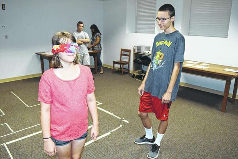 "Jocelyn Smock, 10, (left) receives instructions Saturday from her brother, Aaron Smock, 16, on how to navigate a maze at the 39 Clues Family Party at the Jacksonville Public Library. The event was inspired by ""The 39 Clues"" series of novels. Photo:       Greg Olson 