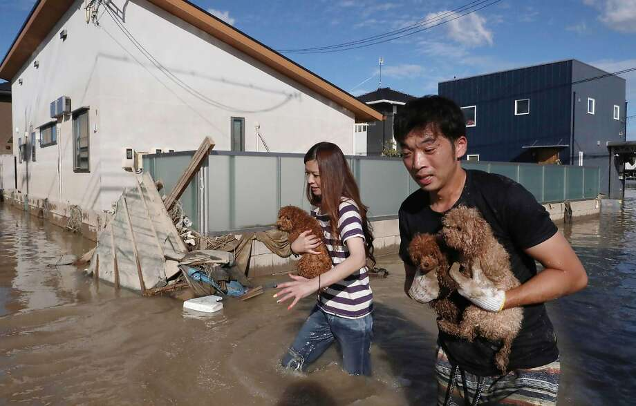Residents rescue dogs from a flooded area in Kurashiki, in western Japan. More than 3 million people have been told to evacuate to safer locations such as school buildings or city shelters. Photo: AFP / Getty Images