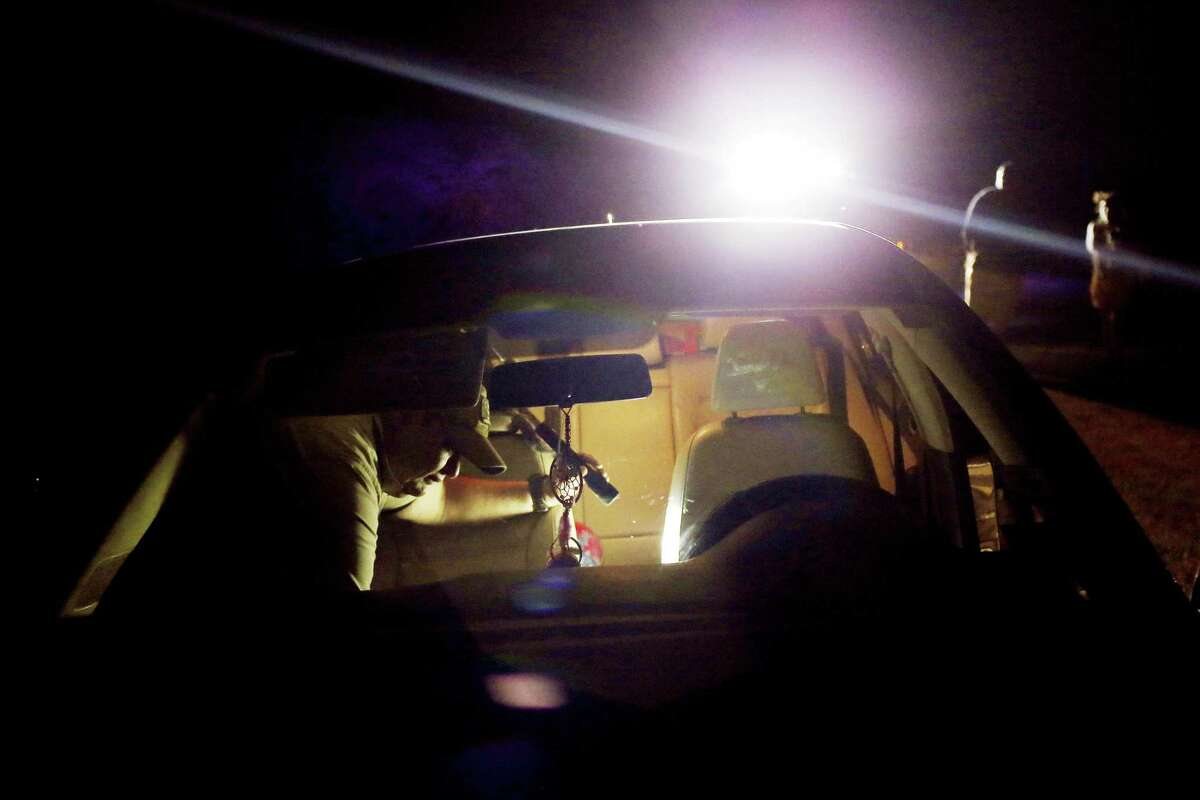 Brooks County Sheriff?•s Deputy Ben Gomez searches a vehicle pulled over on FM 3066 southwest of Falfurrias, Texas, Wednesday, June 27, 2018. The driver and passenger wait in the background. The road is a known pickup area for illegal immigrants walking across ranch lands to avoid the U.S. Border Patrol checkpoint on U.S. 281 south of Falfurrias. Gomez didn?•t find anything illegal in the search. The county is known for its high immigrant death rate due to smugglers moving immigrants through the rugged terrain and extreme temperatures. Through this week, 33 bodies have been found compared to a total of 52 found last year. According to Sheriff Benny Martinez, he expects the body count to increase with the coming of the hottest months of July, August and September.