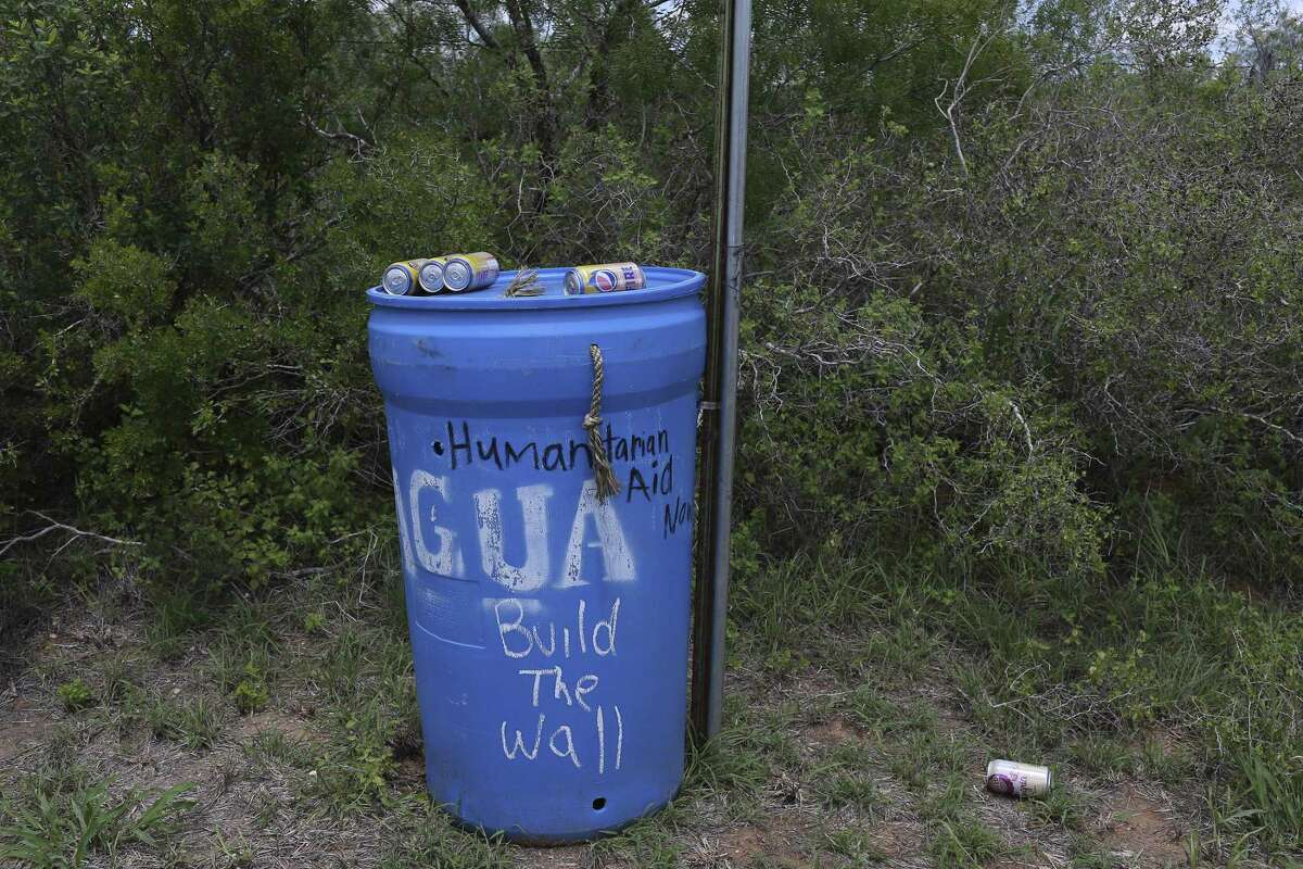 A water station set up for migrants bears graffiti on a farm road in Brooks County. The aid stations are placed along public roads.