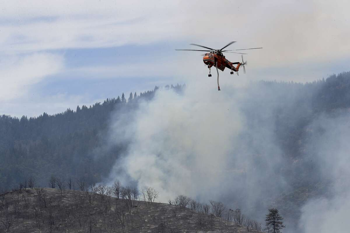 A helicopter flies above the Klamathon Fire near the Oregon-California border and Hornbrook, Calif., Friday, July 6, 2018. California officials say they are temporarily closing a hatchery and two other public areas because of their proximity to a deadly blaze near the Oregon state line. The California Department of Fish and Wildlife says the Iron Gate Fish Hatchery along the Klamath River, the Klamathon Road fishing access below the hatchery and the Horseshoe Ranch Wildlife Area have been closed as a precaution. (Greg Barnette/The Record Searchlight/USA TODAY Network via AP)