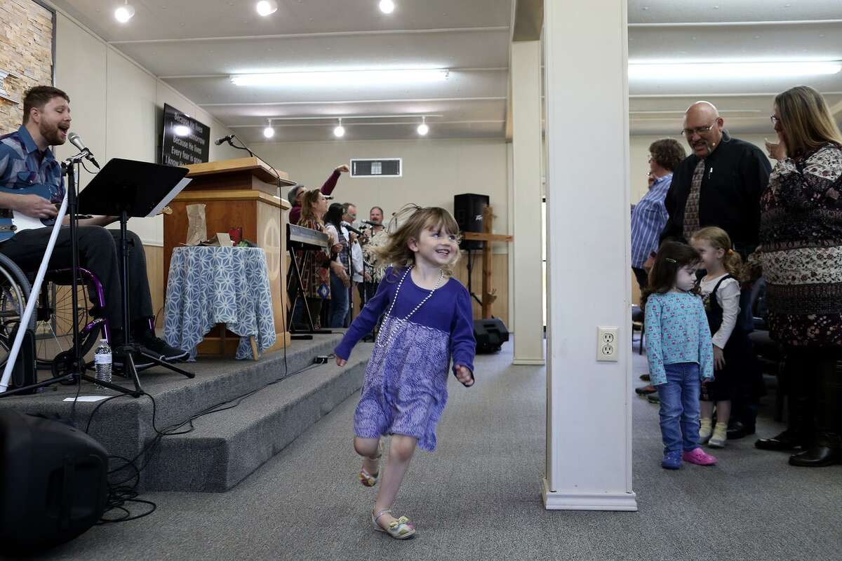 Abigail Goff, 3, dances to the music by worship leader Kris Workman, left, and the praise team during a Sunday service on April 15, 2018. Workman was shot and paralyzed in the shooting at the church Nov. 5. At right is the church's pastor, Frank Pomeroy, and his wife, Sherri Pomeroy, with Kris' daughter, Eevee Workman, right, and Elene Slavin.