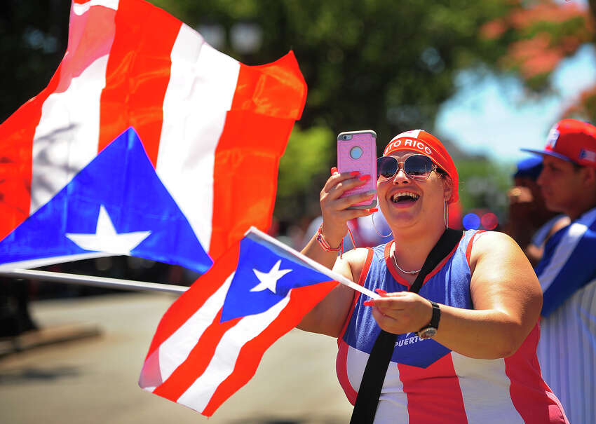 Carmen Aquino, of Bridgeport, gets in the spirit during the Annual Puerto Rican Day Parade on Park Avenue in Bridgeport, Conn. on Sunday, July 8, 2018.