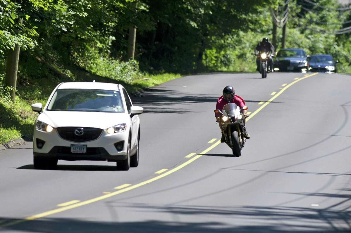 A motorcyclist legally passes a car on Long Ridge Rd. in north Stamford, Conn. on Sunday, July 8, 2018. The recent street paving has resulted in increased speeding and passing.