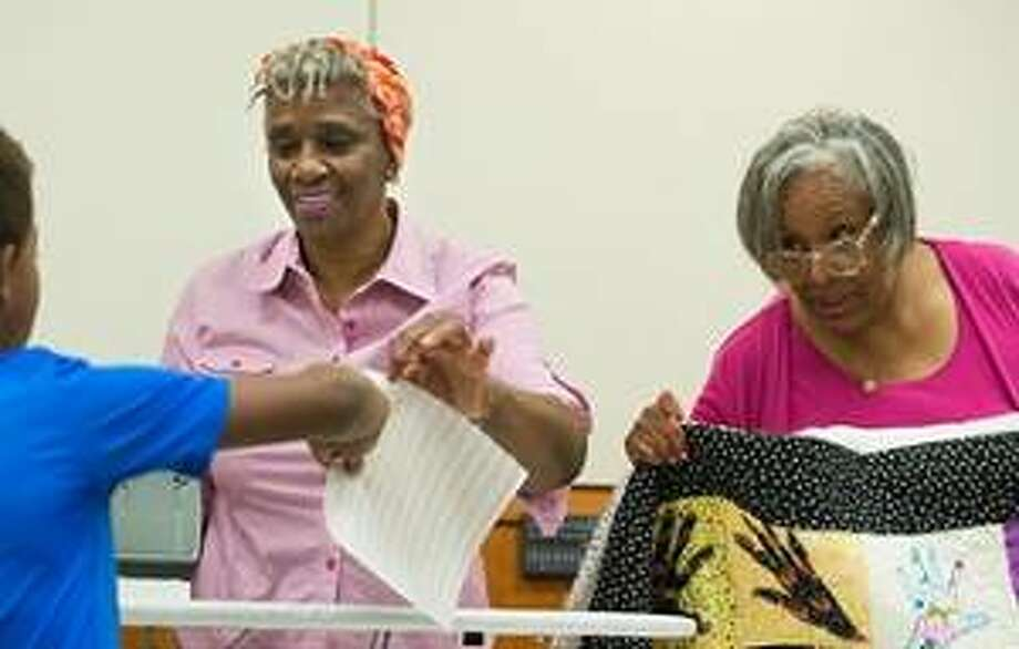 Noted multimedia and fabric artist, quilter and SIUE alumna Edna Patterson-Petty (left) and The Hands of Children Project Coordinator Pamela Coaxum offer assistance with the art of quilting. Photo:       For The Telegraph