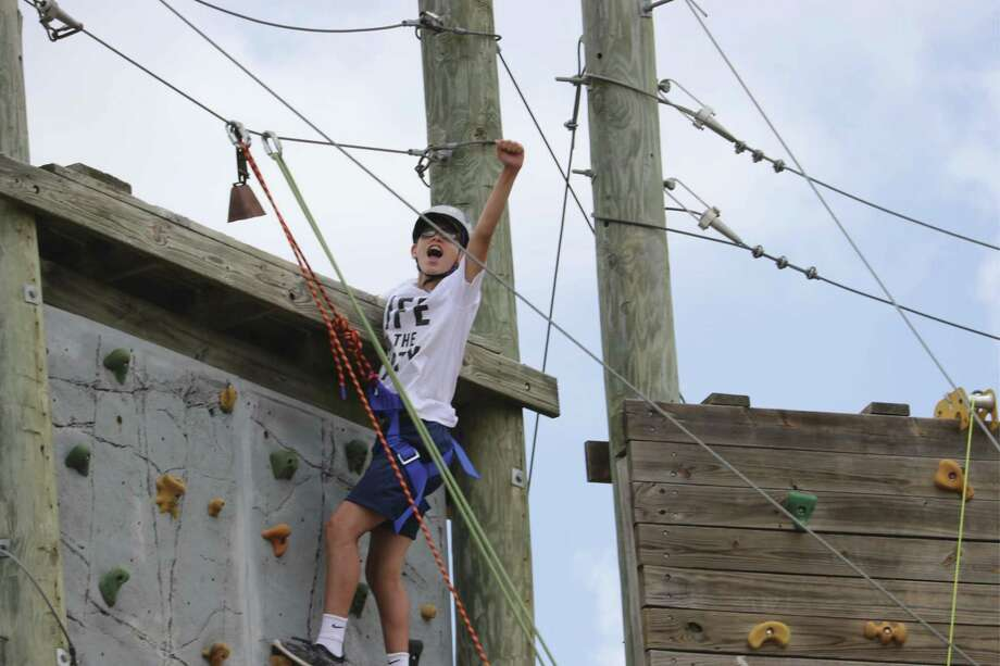 The 'Can Do' attitude is prevalent at the Texas Lions Camp in Kerrville as a camper makes it to the top of the ropes course to rings the bell.