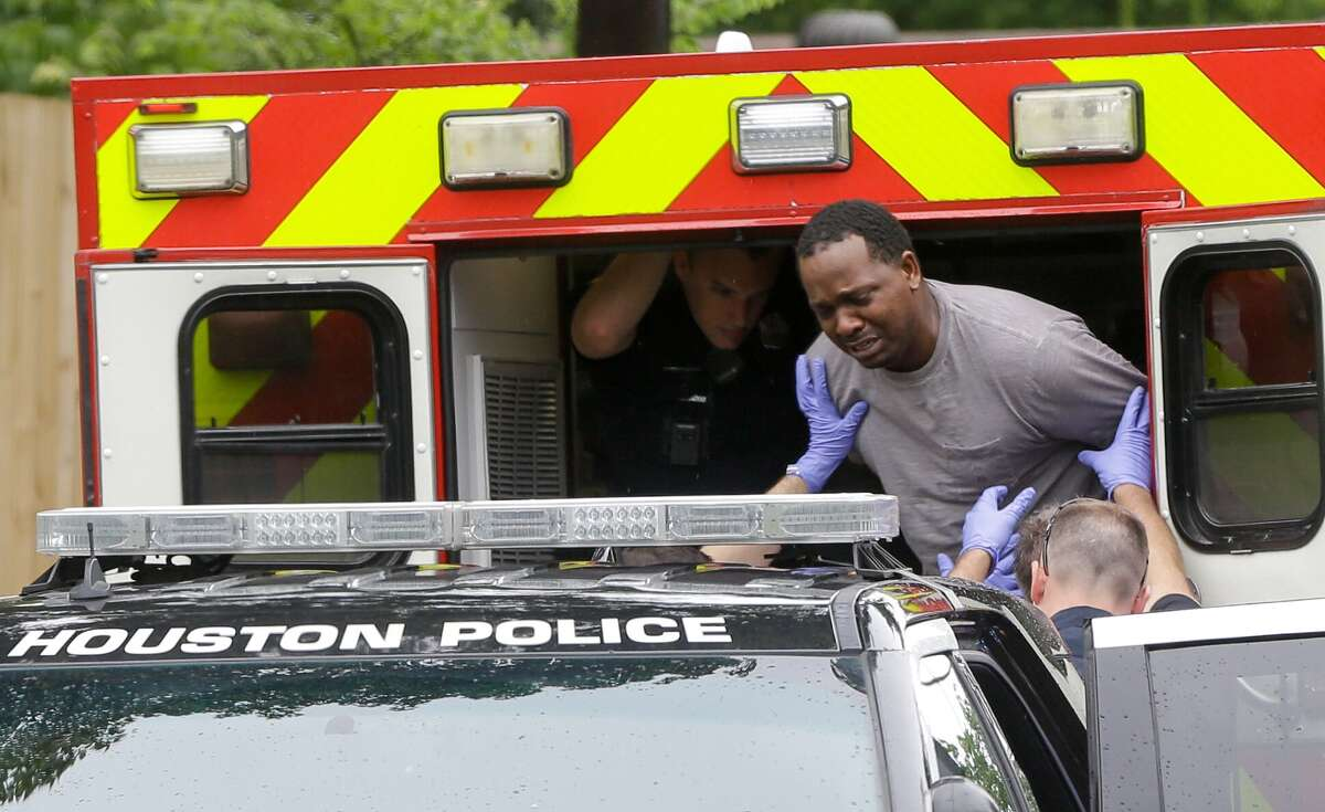 Houston police and medical personnel transfer Christopher Charles Williams Sr. from an ambulance to a patrol car outside his home at 8405 Knox where his two-year-old son, Christopher Charles Williams Jr. was shot July 8, 2018 in Houston. The boy was transported to the hospital but died from the accidental shooting.
