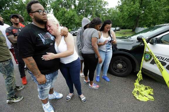 Suzanne Alvarado, center, is comforted as she and other family members and friends wait near the home of her cousin, Christopher Charles Williams Sr., where his two-year-old son, Christopher Charles Williams Jr. was shot July 8, 2018 in Houston. The boy was transported to the hospital but died from the accidental shooting.