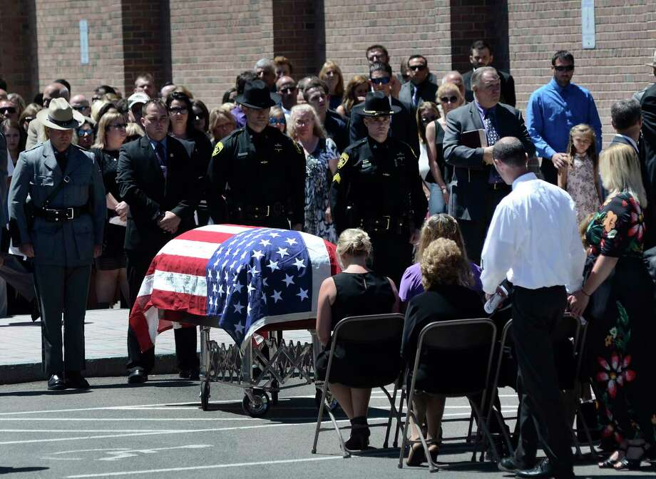 Trooper Nicholas F. Clark's casket sits in front of his family before the flag is folded and handed to his mother during the funeral service in Clark's honor, Sunday, July 8, 2018 at Alfred University in Alfred, N.Y. Clark, 29, was shot and killed July 2 while responding to a suicidal individual in the Corning, N.Y., area. (AP Photo/Heather Ainsworth) Photo: Heather Ainsworth / AP