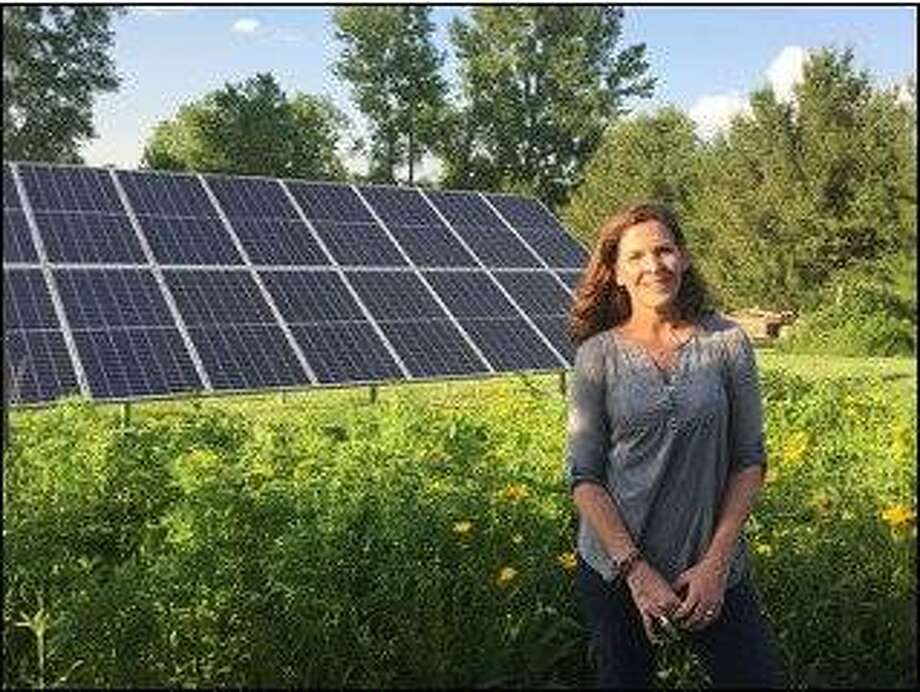 Sheila Voss, Solar Power Hour presenter with Solarize Metro East, stands in front of her ground mounted solar array. Photo:       StraightUp Solar | For The Telegraph