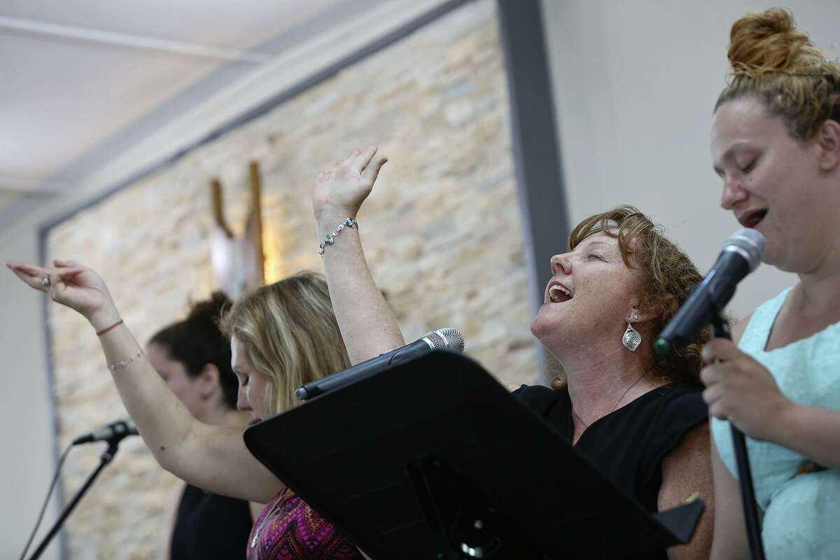 Sheri Kay sings with the worship team and congregation at First Baptist Church of Sutherland Springs on Sunday, July 8, 2018. Kay lost her nephew, Bob Corrigan, and his wife, Shani, in the shooting at the church. Kay is a licensed counselor who works with The Ecumenical Center in an office at the church, helping others with their grief and healing.