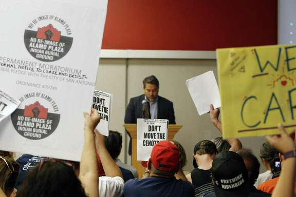 People carrying signs to express their opposition to a plan to redo much of Alamo Plaza attend a June 18 meeting. District 1 City Councilmember Roberto Trevino addresses the crowd. It was the first of four public meetings in June about the proposals.