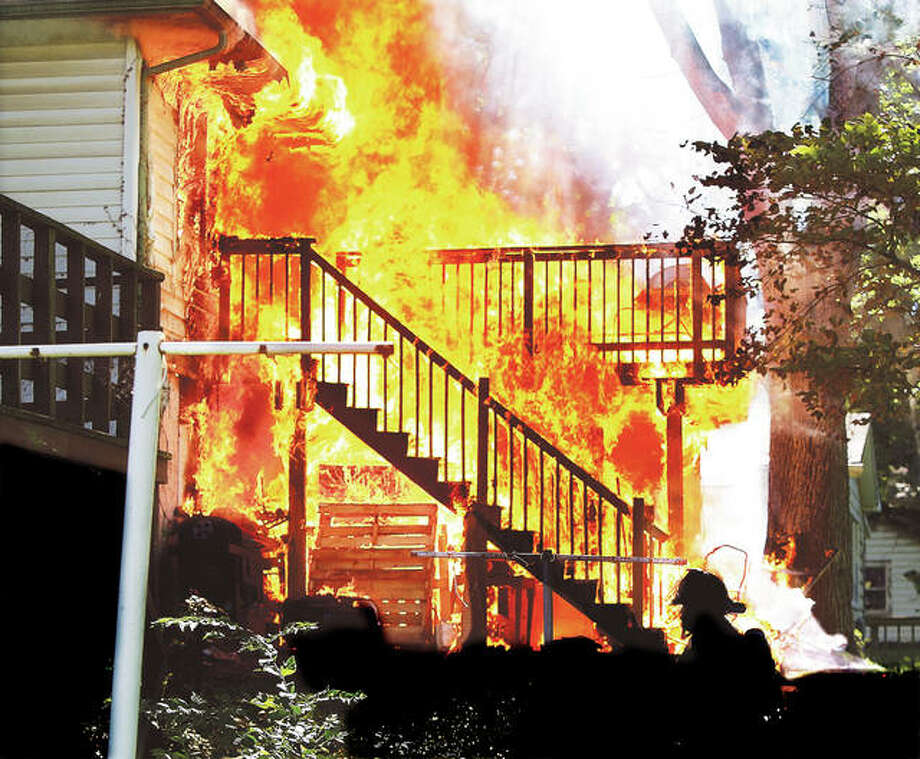 An Alton firefighter, lower right, walks around the fully engulfed rear of 3546 Oscar Ave. in Alton about 4:30 p.m. Saturday after multiple 911 calls were made by neighbors reporting the house was on fire. Black smoke was visible for many blocks as flames consumed the rear porch and spread into the house and basement. East Alton firefighters were called to the scene to assist with the blaze. The interior of the home also suffered extensive smoke and heat damage. All occupants and pets were reported out of the house by the time firefighters arrived. No injuries were reported. The cause of the fire was under investigation Saturday evening. Photo:     John Badman | The Telegraph