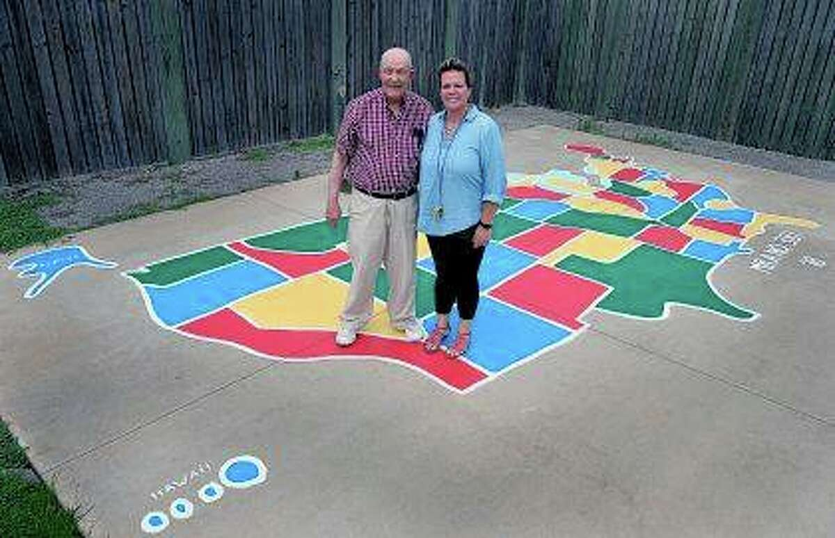 Former elementary school principal Gene Alexander (left) and Lindsey Bullman, executive director of the Night's Shield, a nonprofit children's shelter, show Alexander's most recently completed United States map, his 381st, in West Frankfort. In retirement, Alexander spends time working at his hobby of painting, specifically painting maps of the United States on playgrounds.