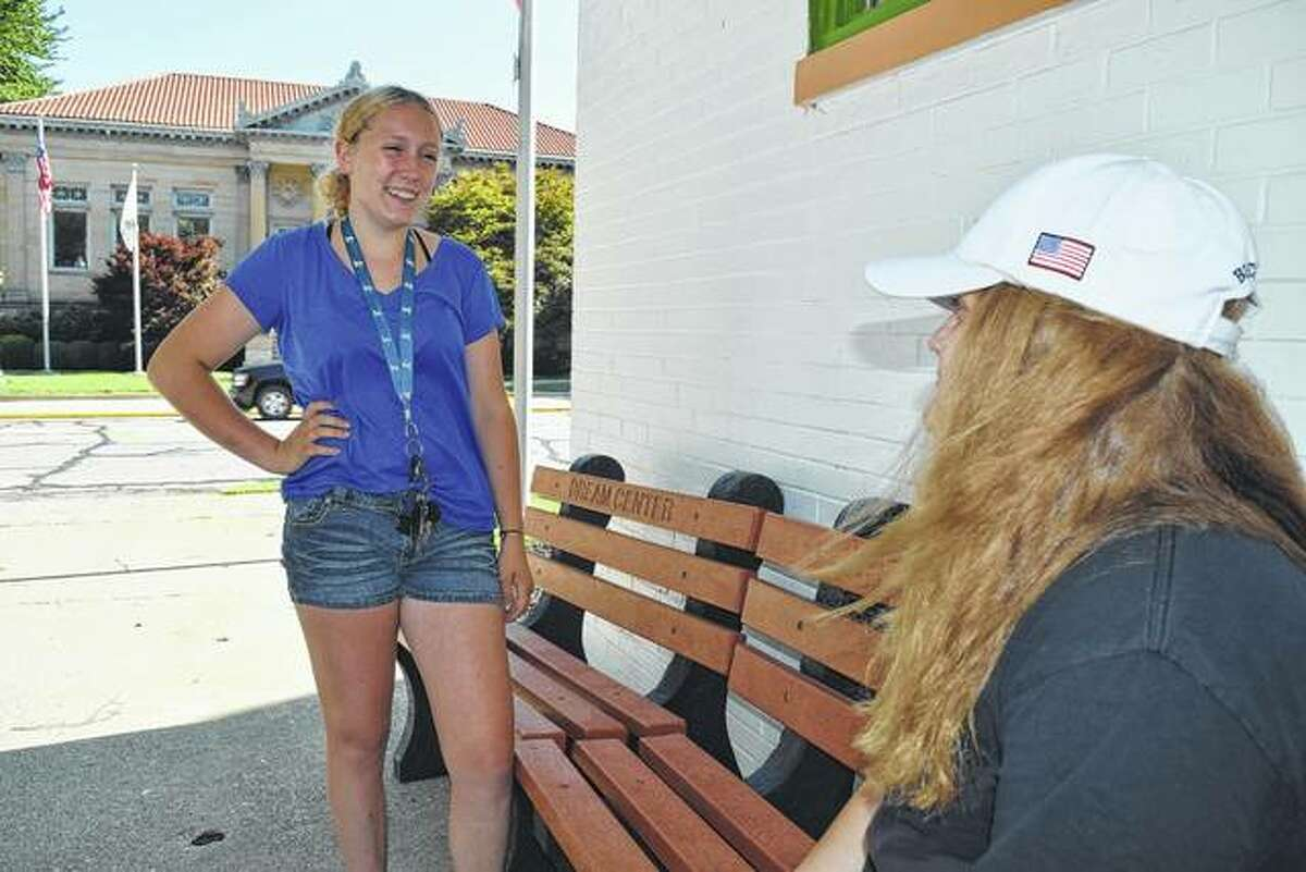 Kayla Critchelow (left), 16, talks with her sister, Jayla Critchelow, 14, outside the Jacksonville Dream Center Foundation's headquarters at 210 W. College Ave. The Critchelow sisters have been active in collecting caps and lids for A Bench for Caps, a community recycling program that has helped make 61 benches, including the two in this photo.