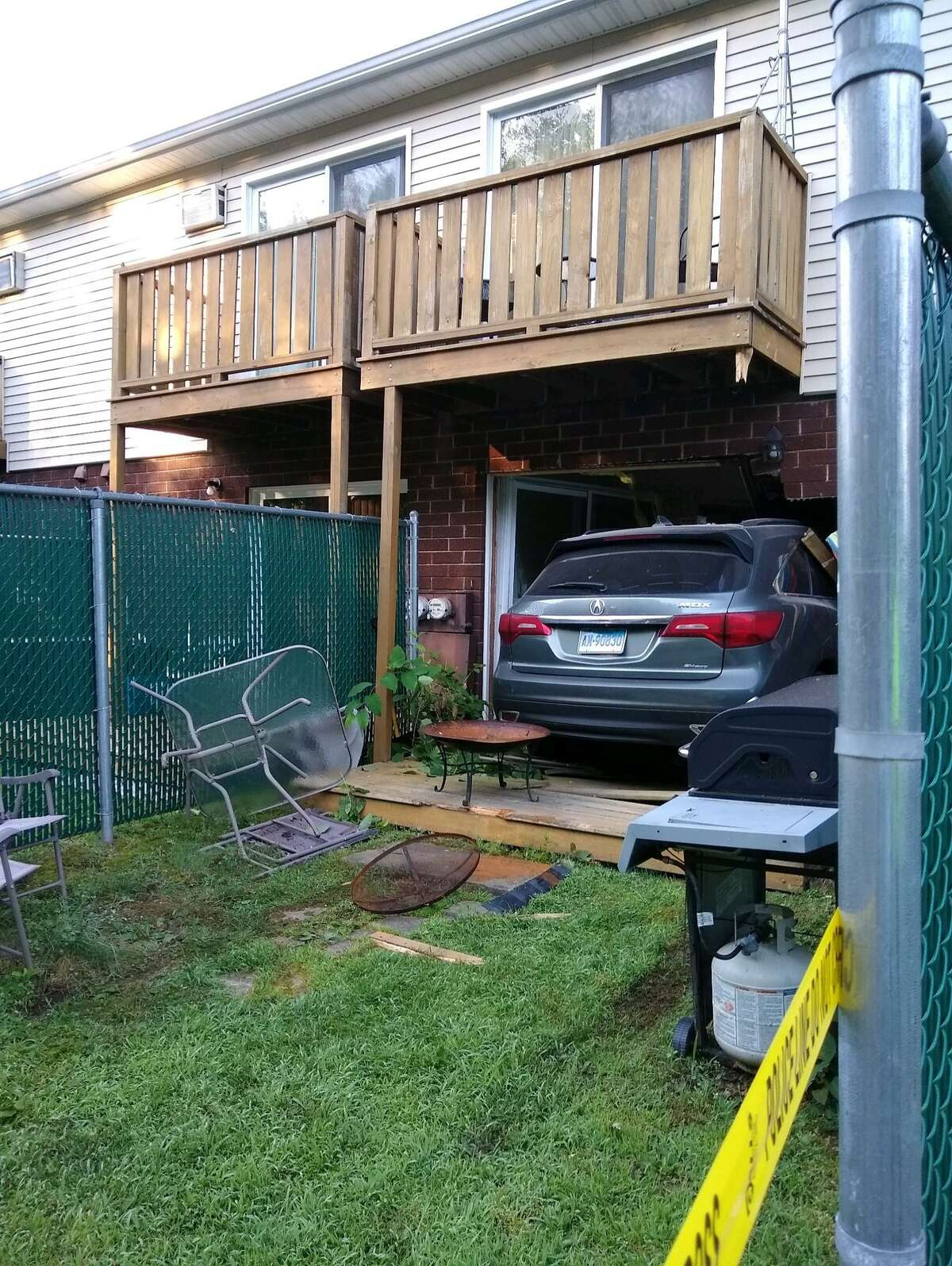 West Haven police say that after being shot, the driver of the car crashed into the apartment complex.