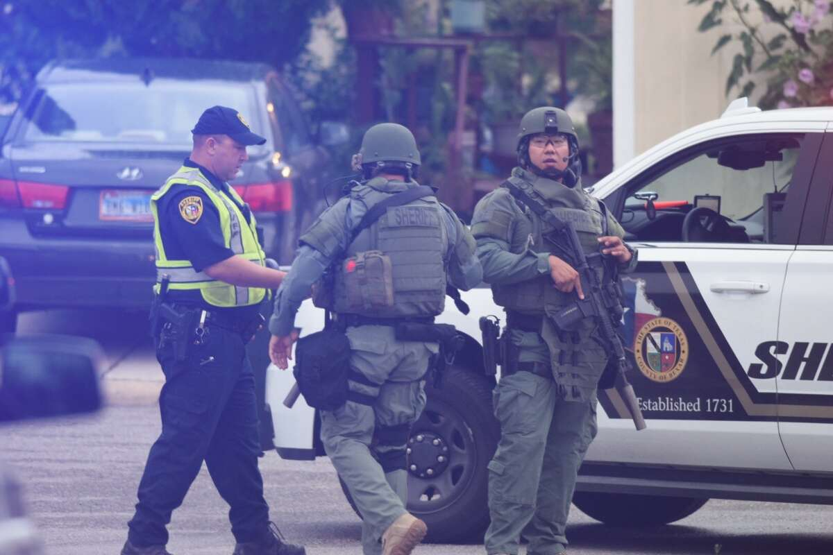 Officials with the Bexar County Sheriff's Office SWAT team surround a residence off U.S. 90 near Kriewald Road the morning of July 9, 2018.