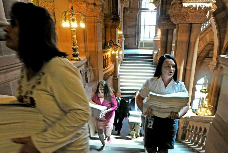 Members of Gov. David Paterson?s staff deliver copies of vetoed bills Wednesday to the state Assembly at the Capitol. The action is drawing a chorus of criticism from lawmakers, but a move override the vetoes is in doubt. Photo: MICHAEL P. FARRELL