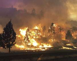 In this photo released Friday, July 6, 2018, by the California Highway Patrol, the Klamathon Fire burns in Hornbrook, Calif. A local California official says a deadly blaze burning near the Oregon border moved swiftly through the rural area that is home to many retirees. Siskiyou County Board of Supervisors chair Ray Haupt says the blaze moved so fast it quickly reached Hornbrook, a community of about 250 people about 14 miles (22 kilometers) south of the Oregon border. Authorities said one person was killed in the fire. (California Highway Patrol via AP)