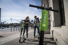 People use a smartphone to LimeBike shared electric scooters on the Embarcadero in San Francisco.