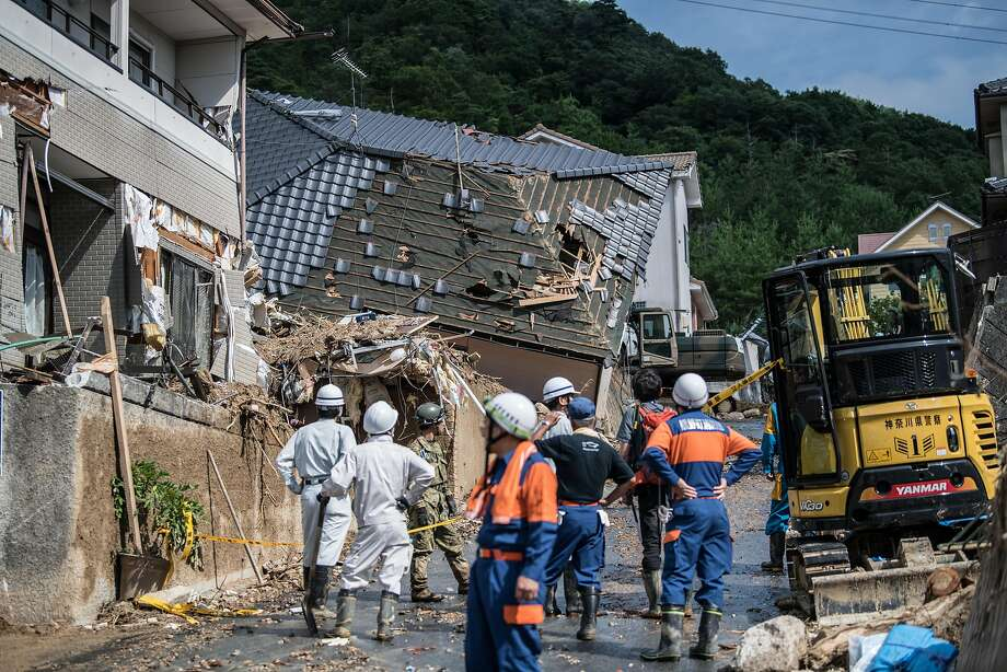 "HIROSHIMA, JAPAN - JULY 09: Emergency services members wait by buildings destroyed by a landslide on July 8, 2018 in Kumano near Hiroshima, Japan. Over 100 people are now believed to have died during floods and landslides triggered by ""historic"" levels of heavy rain across central and western parts of Japan while more than 50,000 rescuers are racing to find survivors as temperatures rise. Japan's Prime Minister Shinzo Abe warned on Sunday of a ""race against time"" to rescue flood victims as almost 2 million people are subject to evacuation orders and tens of thousands remain without electricity and water. (Photo by Carl Court/Getty Images) Photo: Carl Court / Getty Images"