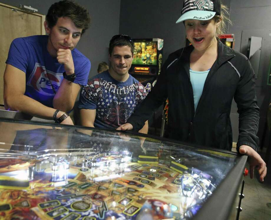 Sabrina Fuller watches her pinball game at What's Brewing? coffeehouse as James Vickers (left) and Brandon Fuller look on. What's Brewing? has more than 20 pinball machines, and is one of those rare old-school arcades in San Antonio. Photo: Tom Reel /San Antonio Express-News / 2017 SAN ANTONIO EXPRESS-NEWS
