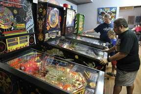 David Sarran plays a board while Elliot Poduska shows his son Bennett how to play as customers play pinball machines at What's Brewing? coffeehouse.