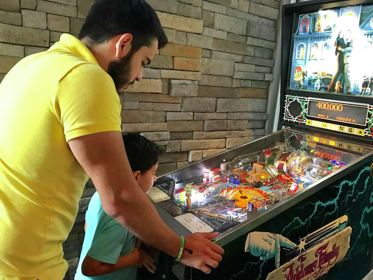 Pedro Torres plays a game of pinball with his 6-year-old nephew, Renzo Alanis, at TBD Bar + Social. TBD has a couple of pinball machines among its many board games and other diversions for patrons.