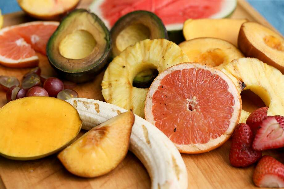 Sliced avocados, pineapple, grapefruit, peaches, mangoes, seedless red grapes, watermelon and bananas are taken fresh from the smoker with noticeable color taken in from the apple wood. Photo: Marvin Pfeiffer /San Antonio Express-News / Express-News 2018