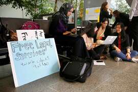Several groups including Zahra Billoo, (center) with the Council on American-Islamic Relations offered free legal information to arriving passenger as the federal government implements the travel ban on people arriving from six mostly Muslin countries, at San Francisco International airport on Thursday June 29, 2017 in San Francisco, Ca.