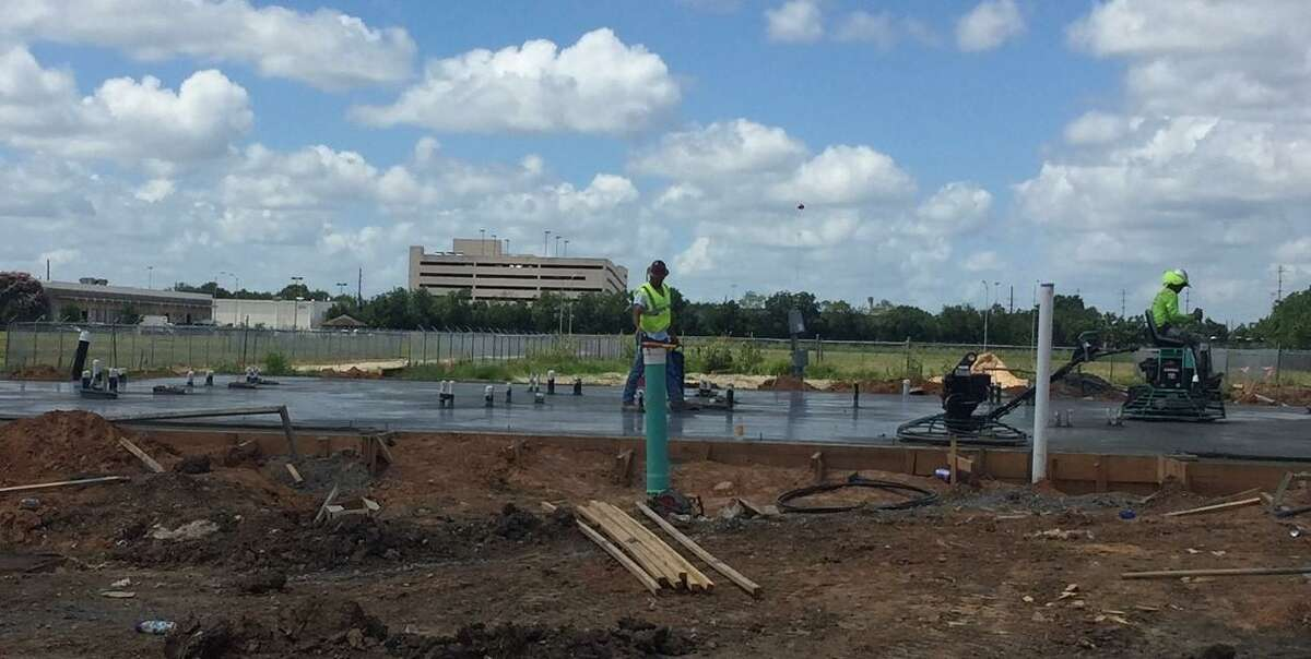Worker pour concrete on the foundation for the new Halo House on June 27.