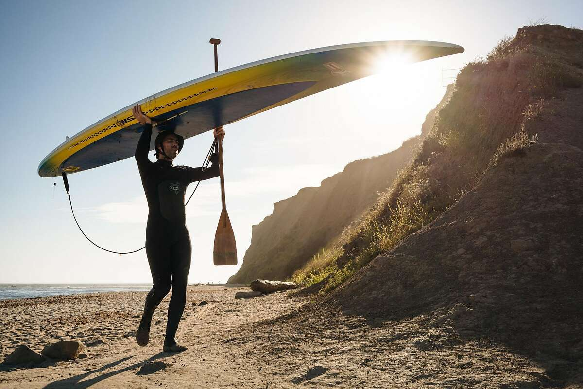Tim McGhee hauls his stand up paddle board across the beach after finishing paddling around the Maverick Beach coastline in Half Moon Bay, Calif., on Saturday, July 7, 2018.