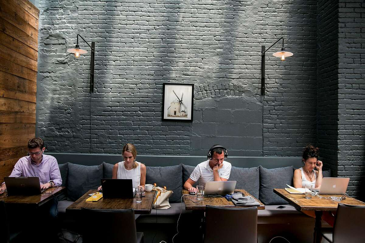 Members of Spacious work from the dining area of The Milling Room, in New York, June 29, 2018. Spacious, a membership-based startup, converts upscale restaurants into weekday workspaces. (Sam Hodgson/The New York Times)