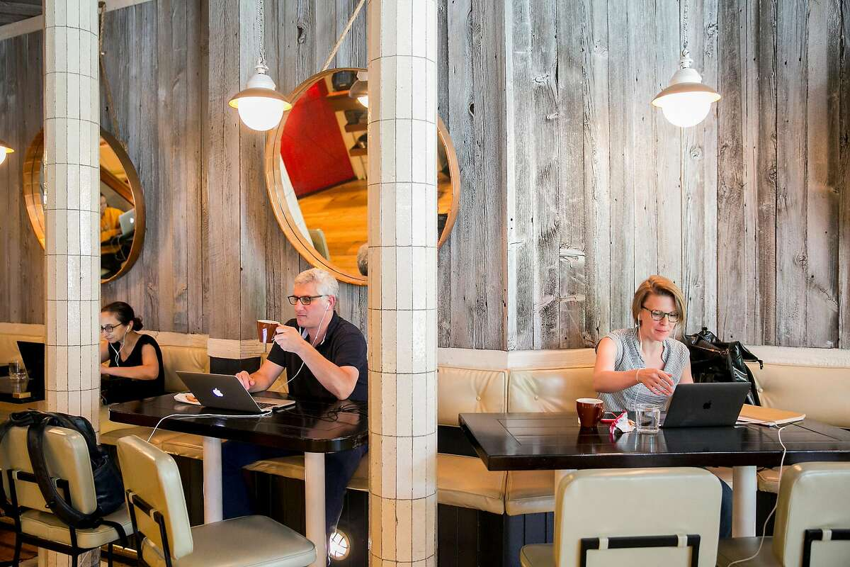 Members of Spacious work at Crave Fishbar in New York, June 29, 2018. Spacious, a membership-based startup, converts upscale restaurants into weekday workspaces. (Sam Hodgson/The New York Times)