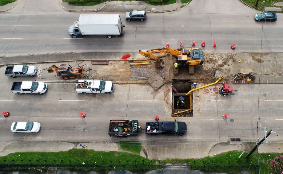 Construction workers repair a sinkhole on South Post Oak Road near Gasmer Drive Monday, July 9, 2018, in Houston.