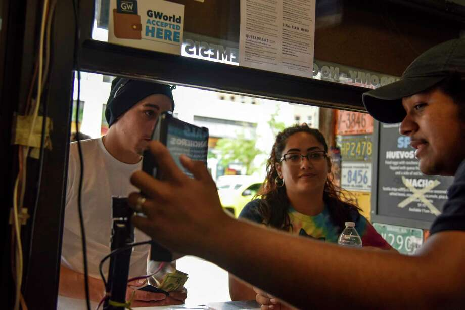 After pulling out cash to pay for food, customers Aaron Bateman and Roxann Barr, hear from cashier Obed Amaya that Surfside, a taco/burrito walk-up only restaurant, does not accept cash. Photo: Washington Post Photo By Jahi Chikwendiu / The Washington Post