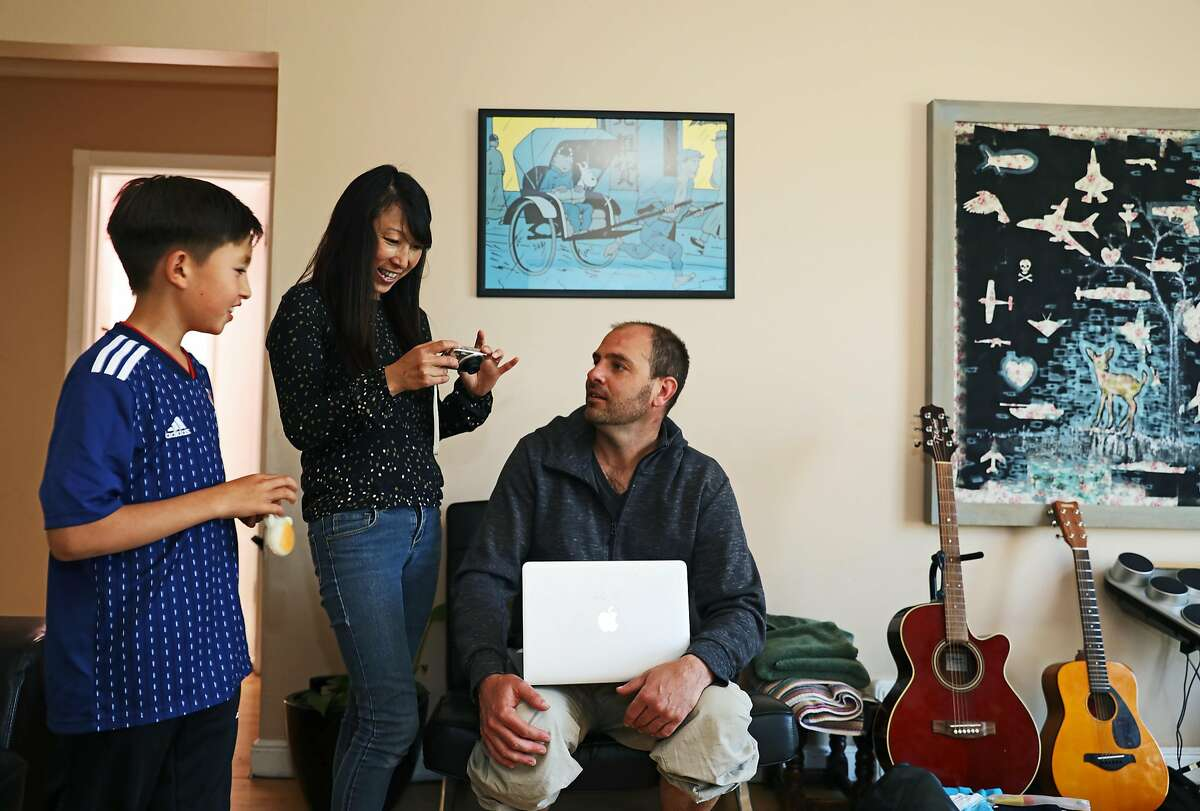 """(Names cq'd from left to right) Kosei, 10, Yuki, 47, and Kyle Retzik, 43, attempt to troubleshoot a camera in their home in San Francisco, California on Saturday, July 7, 2018. The family is experiencing a difficult situation after their original landlord was foreclosed and an LLC purchased the property. The company has nearly doubled their rent after realizing they couldn't evict the Retzik's without just cause. """"It's definitely stressful. These aren't like people who are like a family who bought the house and now they're going to move in here,"""" said Kyle Retzik. """"This is like a nameless LLC that is not even from San Francisco -- they're from LA-- that are essentially real estate speculators. They want to buy and flip this house instead of having a family live here."""" The Retzik's have managed to pay the rent increase for the last two months. """"It's not easy and it makes me nervous,"""" said Yuki Retzik."""