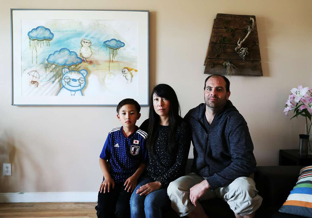 """(Names cq'd from left to right) Kosei, 10, Yuki, 47, and Kyle Retzik, 43, pose for a portrait in their home in San Francisco, California on Saturday, July 7, 2018. The family is experiencing a difficult situation after their original landlord was foreclosed and an LLC purchased the property. The company has nearly doubled their rent after realizing they couldn't evict the Retzik's without just cause. """"It's definitely stressful. These aren't like people who are like a family who bought the house and now they're going to move in here,"""" said Kyle Retzik. """"This is like a nameless LLC that is not even from San Francisco -- they're from LA-- that are essentially real estate speculators. They want to buy and flip this house instead of having a family live here."""" The Retzik's have managed to pay the rent increase for the last two months. """"It's not easy and it makes me nervous,"""" said Yuki Retzik."""