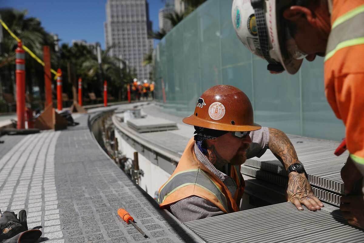 Laborers Charles Ruland (l to r) and Filiberto Jasso work on the Bus Jet Fountain in the Rooftop Park at the Salesforce Transit Center on Monday, July 9, 2018 in San Francisco, Calif.