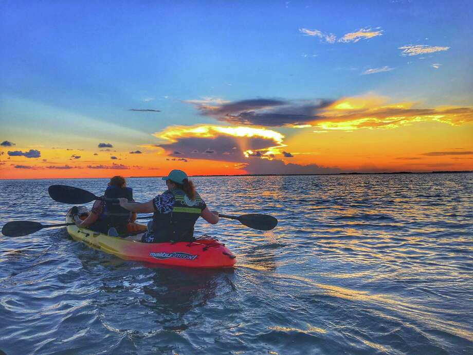 Two of Bobbie Blouin's friends, Dodie Maddox, back, and Lorna Meyer, front, paddle into the sunset at the end of a two-hour kayaking tour in Galveston Bay. Photo: Courtesy Bobbie Blouin