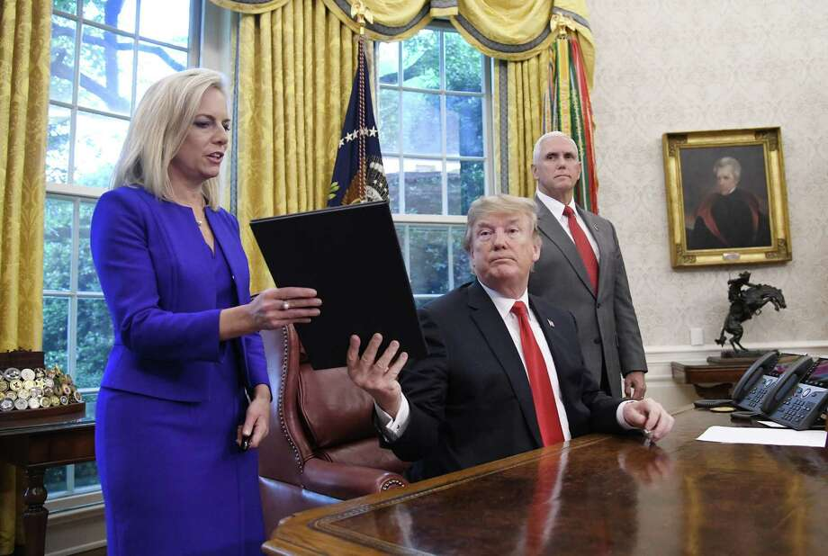 President Donald Trump gives a signed executive order to keep families together at the border to Homeland Security Secretary Kirstjen Nielsen, left, in the Oval Office of the White House on June 20. , 2018. However, the zero-tolerance policy that prompted family separations is still in place, a sign over the president's overt antipathy toward non-white immigrants. Photo: Olivier Douliery /TNS / Abaca Press