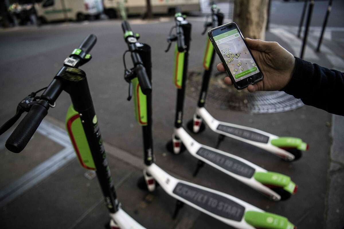 A man shows the mobile application allowing to check the availability of electric scooters of the US company Lime on the day of their launch in Paris on June 22, 2018. / AFP PHOTO / Christophe ARCHAMBAULTCHRISTOPHE ARCHAMBAULT/AFP/Getty Images
