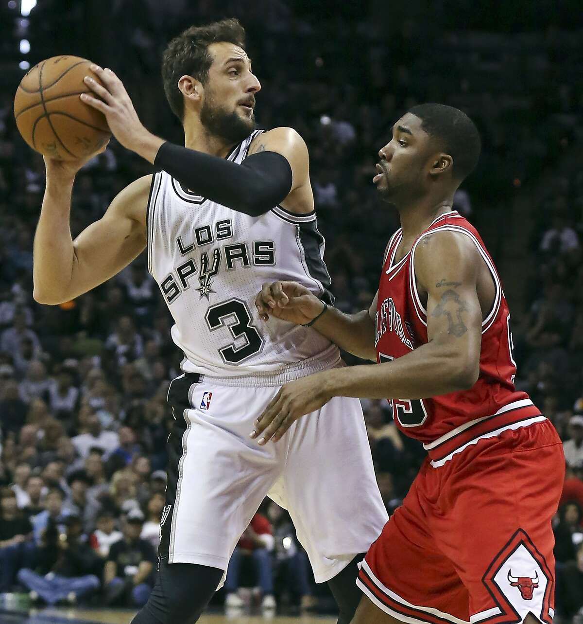 San Antonio Spurs' Marco Belinelli looks to pass around Chicago Bulls' E'Twaun Moore during second half action Sunday March 8, 2015 at the AT&T Center. The Spurs won 116-105.