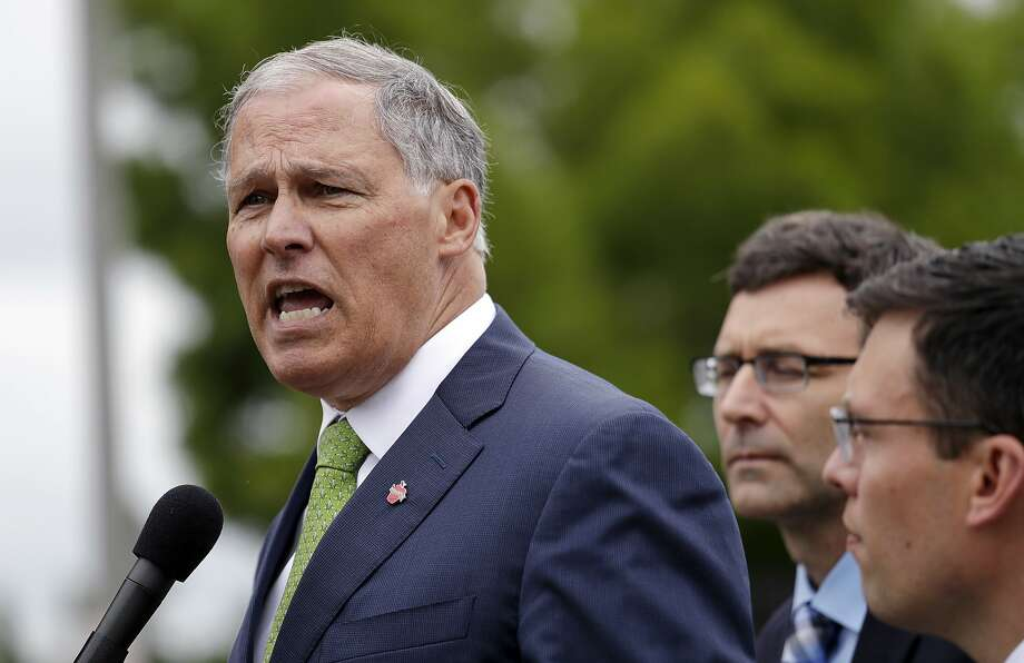 Washington Gov. Jay Inslee speaks as state Attorney General Bob Ferguson, center, and Solicitor General Noah Purcell look on at a news conference announcing a lawsuit against the Trump administration over a policy of separating immigrant families illegally entering the United States, in SeaTac, Wash., on June 21. Photo: Elaine Thompson / Associated Press