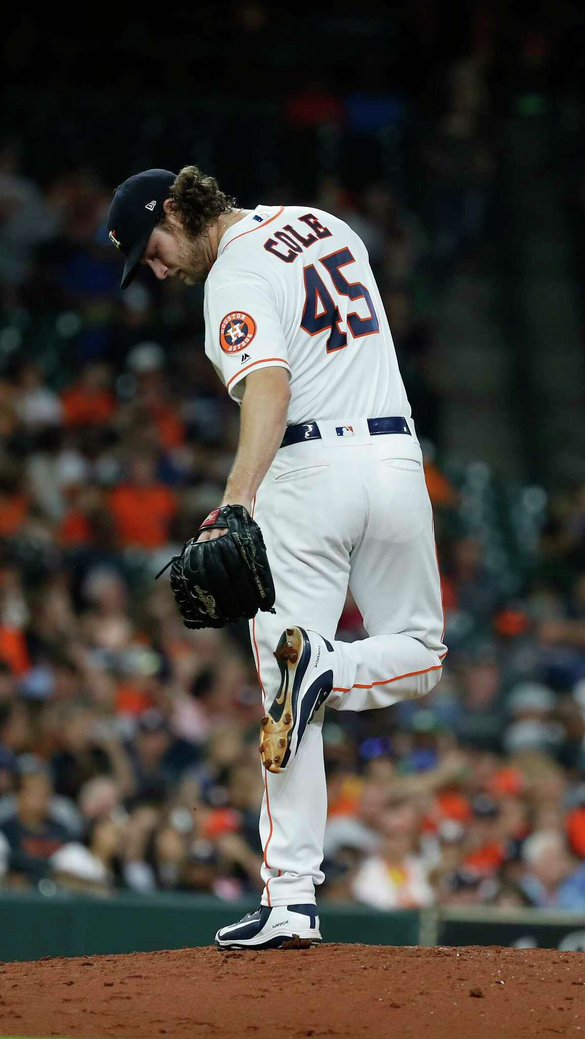 Houston Astros starting pitcher Gerrit Cole (45) checks the mud on his shoes between pitches during the fourth inning of an MLB game at Minute Maid Park, Monday, July 9, 2018, in Houston.