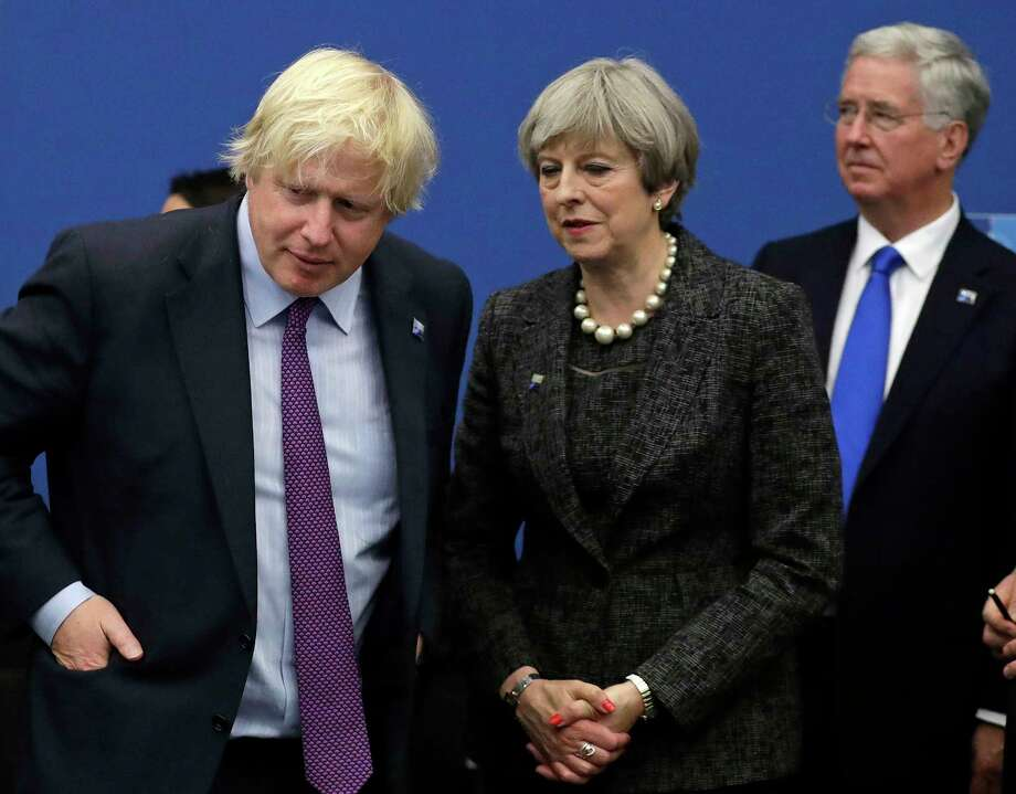 FILE - In this file photo dated Thursday, May 25, 2017, British Prime Minister Theresa May talks with British Foreign Minister Boris Johnson, with British lawmaker Michael Fallon, right, as they participate in a NATO summit of heads of state and government in Brussels. Prime Minister Theresa May has accepted the resignation of Boris Johnson Monday July 9, 2018, amid Cabinet splits over Brexit. (AP Photo/Matt Dunham, FILE) Photo: Matt Dunham / Copyright 2017 The Associated Press. All rights reserved.